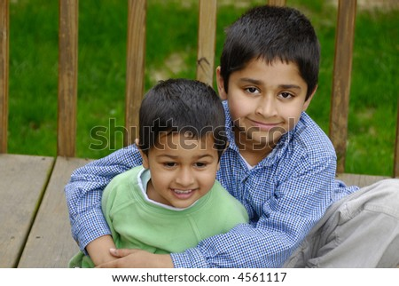 Two Indian brothers happily hugging each other - stock photo