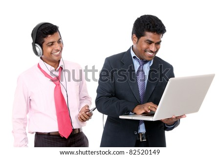 Two indian business people, one is working other one is listening music on white. - stock photo