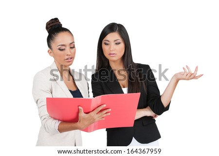 Two Indian business woman discussing documents. While standing isolated on white  - stock photo