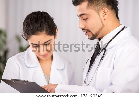 Two Indian doctors sitting working  together