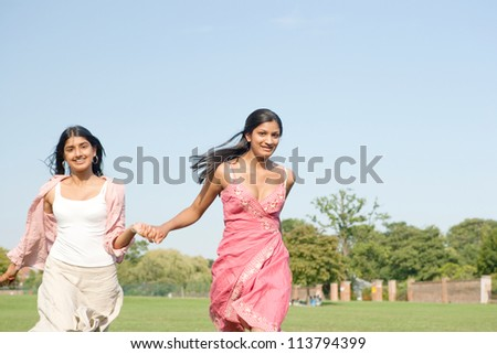 Two Indian girls running in the park while holding hands with a blue sky in the background.