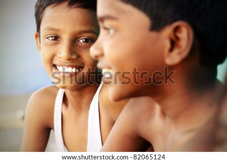 Two Indian happy teen boys posing to the camera.
