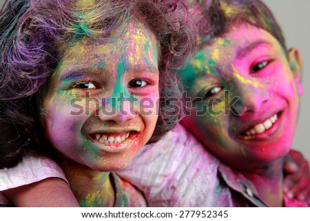 Two Indian kids with face smeared with colors. Concept for Indian festival Holi. - stock photo