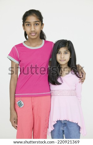 Two Indian sisters hugging - stock photo