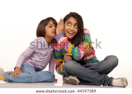two indian sisters sharing secrets to each other - stock photo
