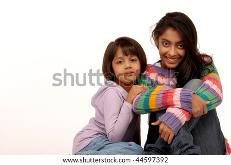 Two indian sisters sitting together - stock photo