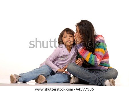 two indian sisters whispering secrets to each other - stock photo