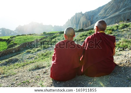 Two Indian tibetan old monks lama in red color clothing sitting in front of mountains - stock photo