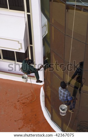 two indian window cleaners cleaning windows of a hotel facade
