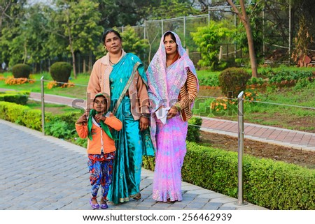 Two indian women with child at the streets of New Delhi, India. 21 February 2013.   - stock photo