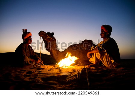 Two indigenous Indian men resting by the bon fire with their camel. - stock photo
