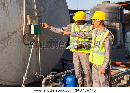 two industrial engineers inspection fuel tank in chemical plant - stock photo