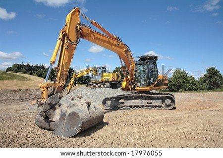 Two industrial sized diggers standing idle on a building construction site in rural countryside with a blue sky to the rear. - stock photo
