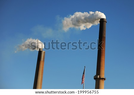 Two industrial smokestacks polluting air over blue sky - stock photo