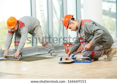 Two industrial tiler builder worker installing floor tile at repair renovation work - stock photo
