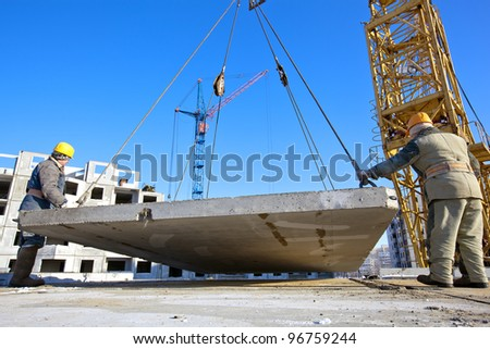 Two industrial workers with hardhats and uniform unloading concrete plate from crane at construction site during the erection of multistory building - stock photo