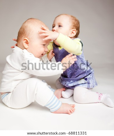 Two infant friends playing, over gray - stock photo