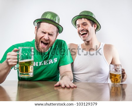 Two Irish friends getting drunk on Saint Patrick's Day in bar together laughing cracking up over beer - stock photo