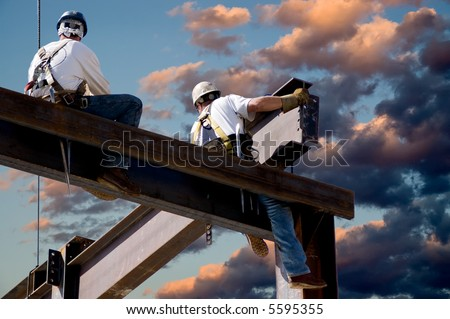 Two ironworkers atop the skeleton of a modern building. One man is positioning a very large beam while the other watches. - stock photo