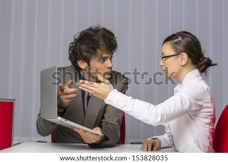 Two irritated business partners arguing and gesturing while trying to solve business problems at work. - stock photo