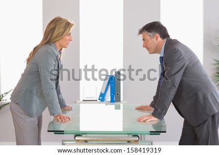 Two irritated businesspeople standing arguing on each side of a desk at office - stock photo