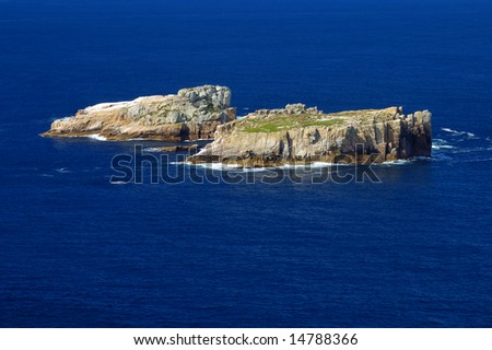 Two isolated and uninhabited rocky islands in the deep blue sea, off the coast of Tasmania, Australia. Space for text on the sea. - stock photo