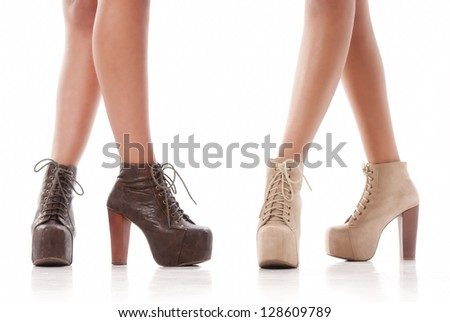Two isolated pair of woman legs with fashion shoes on white background - stock photo