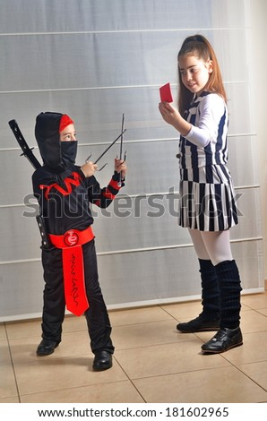 Two Israeli siblings: a 12--year-old teenager girl and a 6-year old boy dressed up for Halloween / Purim as soccer (football) referee and a Ninja Samurai, demonstrating moves with a sword and red card - stock photo