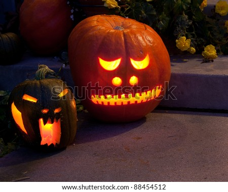 Two jack-o-lanterns are glowing from candles inside, on the front porch, ready for Halloween - stock photo