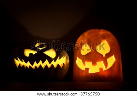 Two Jack-o'-lanterns, Halloween pumpkin faces glowing in the night.