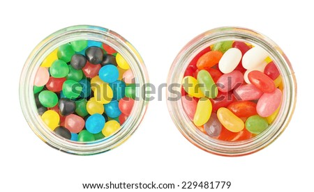 Two jars full of different kinds of candies, isolated over the white background, top view above foreshortening - stock photo