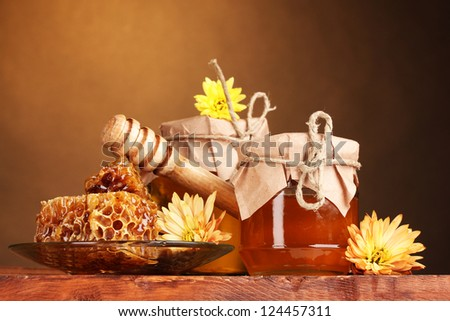 two jars of honey,honeycombs and wooden drizzler on table on yellow background - stock photo