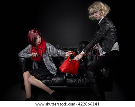 Two jealous fashionable women fighting over red hand bag on a black couch.  They are pulling and tugging on the purse because of envy.
