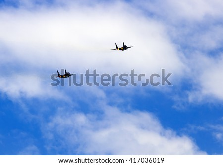 Two jet fighter planes climbing flight, rear view, over cloudy blue sky - stock photo