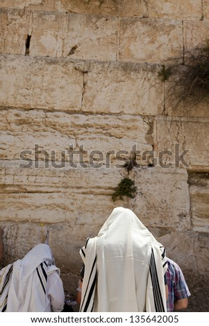 Two Jewish men wearing Jewish praying Shawls standing and parying in front of the wailing wall in the old city of Jerusalem. - stock photo
