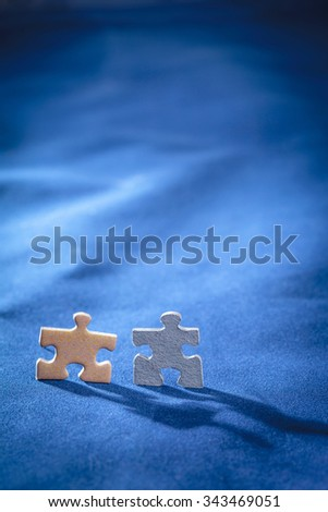 Two jigsaw puzzle pieces in shape of a man over blue background - stock photo