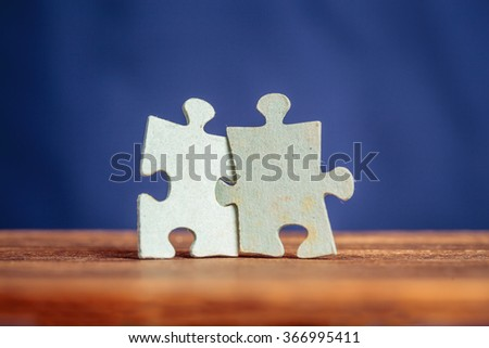 Two jigsaw puzzle pieces on a table joint together. Shallow depth of field - stock photo