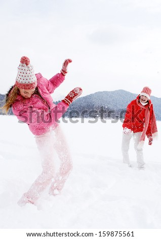 Two joyful and energetic friends playing games and having fun, having a snow ball fight in the snow mountains landscape during a skiing holiday on a sunny winter day, outdoors. - stock photo