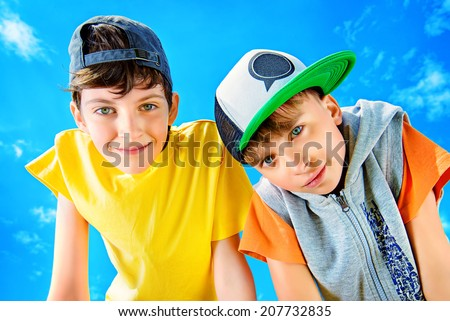 Two joyful boys looking at the camera against the blue sky. Summer. - stock photo