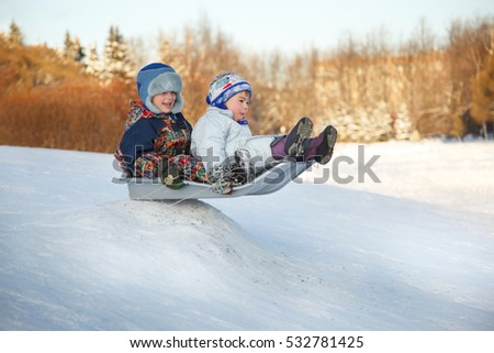 Two joyful childred sledding down the hills in a winter day.