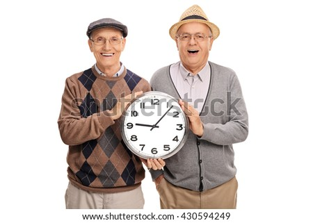 Two joyful elderly men holding a big clock and looking at the camera isolated on white background