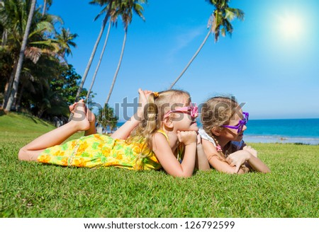 two joyful girls are lying on green grass and looking at the sea - stock photo