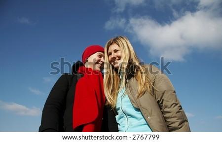 Two joyful girls on blue background - stock photo
