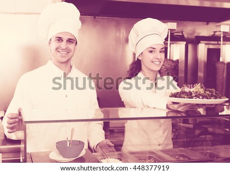 Two joyful professional chefs preparing kebab and vegetables salad at bistro. Focus on man