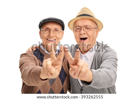 Two joyful senior gentlemen making peace sign with their hands isolated on white background - stock photo