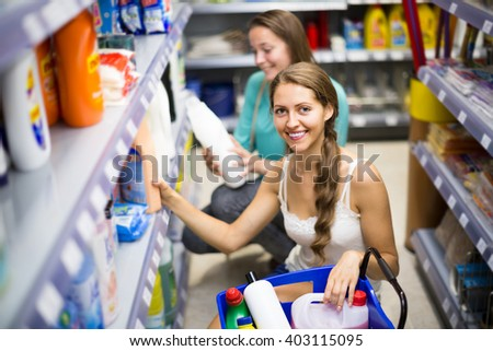 Two joyful smiling adult girls selecting detergents at the household store