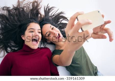 Two joyful teenager girl friends laying on the floor taking a selfie - stock photo