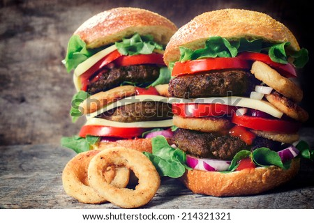 Two juicy double beef burgers and onion rings,selective focus  - stock photo