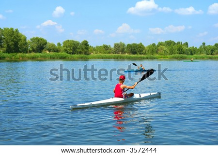 Two kayakers, boy and girl, meet on river (soft focus on boy in red). Shot in June, near Dnieper river, Ukraine. - stock photo