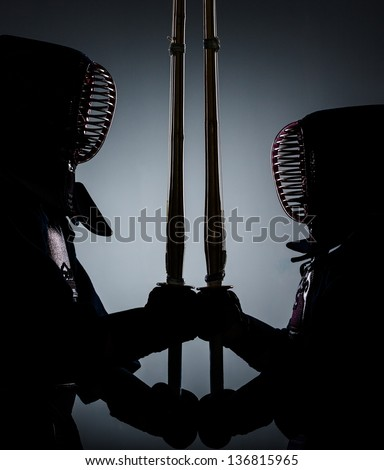 Two kdark endo fighters opposite each other with bamboo sword. Japanese martial art of sword fighting - stock photo